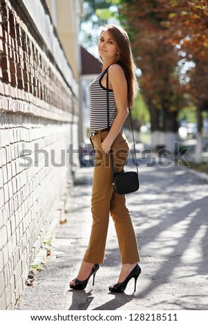 A girl in a striped T-shirt posing on the street