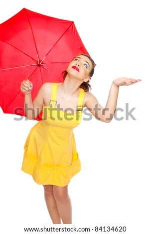 A girl in a summer dress yellow with a red umbrella posing in studio on white background