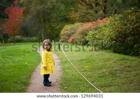 A girl in a yellow coat standing in autumn park - stock photo