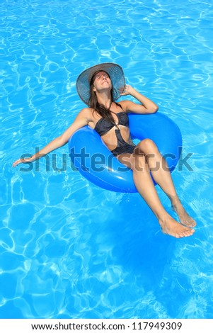 a girl in bikini and hat is in the water