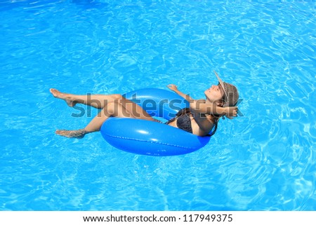 a girl in bikini and hat is in the water - stock photo