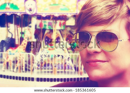 a girl in front of a merry go round done with a retro vintage instagram filter - stock photo