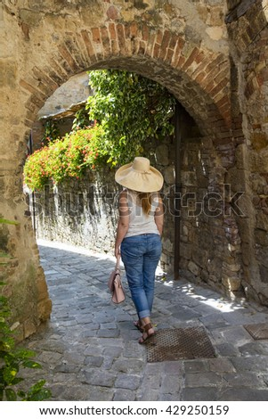 a girl in hat under stone arch in Tuscany in Italy