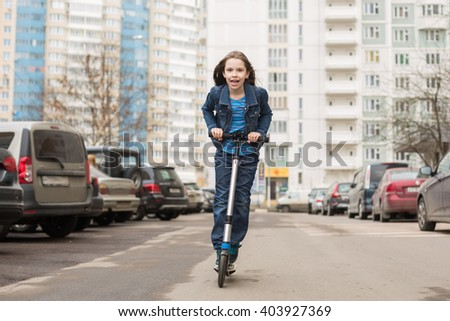 A girl in jeans suit riding a scooter on road parking.