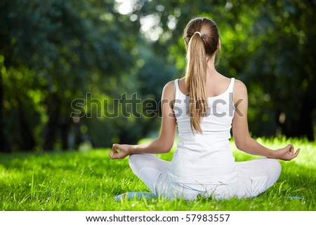 A girl in one of the yoga postures back outdoors - stock photo