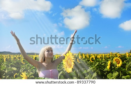A girl in sunflower field enjoys her being - stock photo