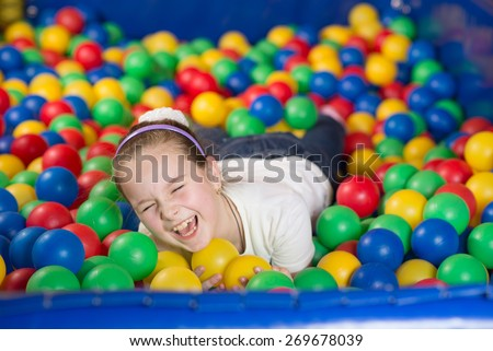 A girl in the playing room with many little colored balls. Close portrait - stock photo