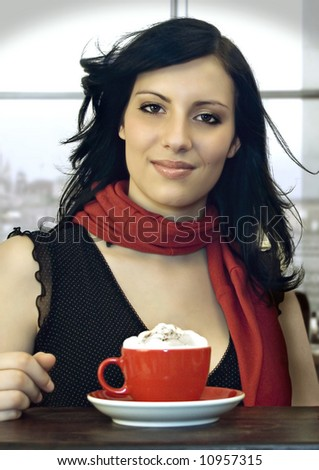 a girl is drinking coffee in a cafeteria - stock photo