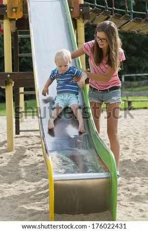 A girl is helping a small child down a tall slide. - stock photo