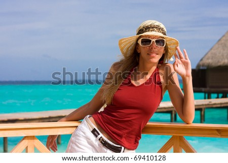 A girl is in red on a beach - stock photo
