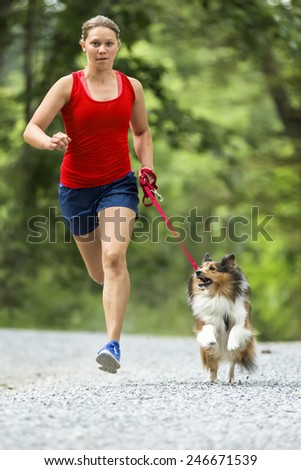 a girl is jogging with her dog - stock photo