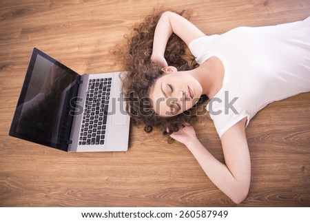 A girl is laying on the floor and is sleeping near a laptop. View from above.