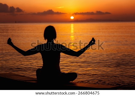 A girl is meditating at the sea shore at orange sunset background.