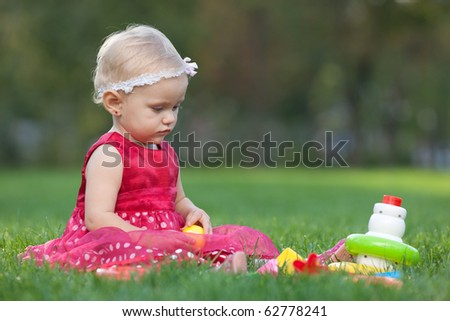 A girl is playing with toy pyramid on the grass in the park