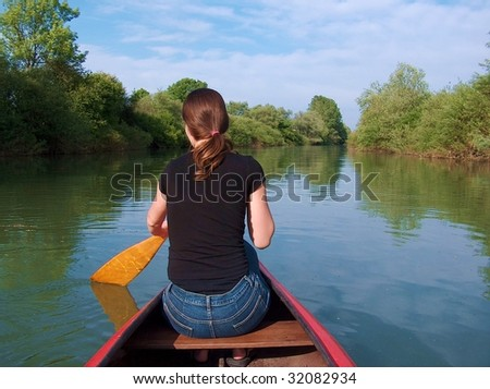 A girl is rowing in a canoe on a green river on a sunny day.