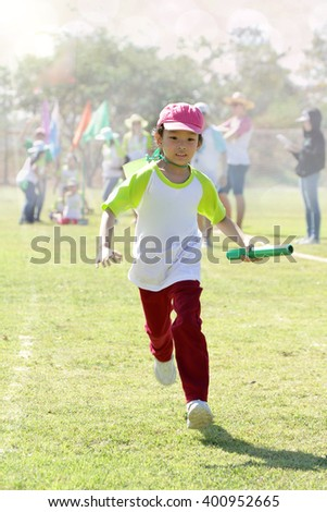 A girl is running quickly to win relay race on her school's sport day. - stock photo