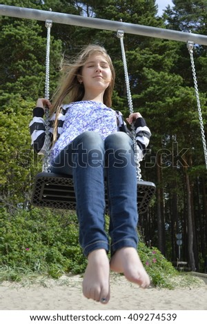 A girl is swinging  with long blond hair fluttering all around. - stock photo