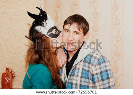 A girl kisses a guy in a mask on the cheek