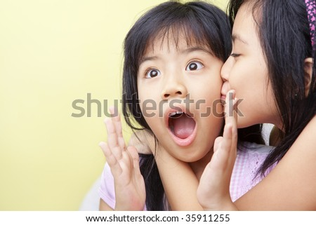 A girl kissing her little sister that look surprised - stock photo