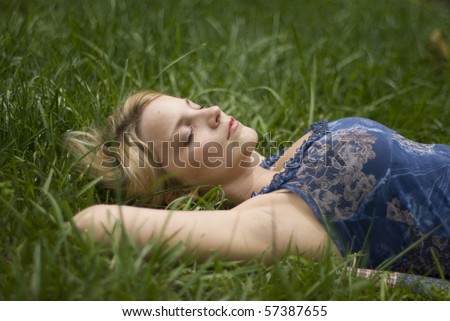 A girl laying in a grass field - stock photo