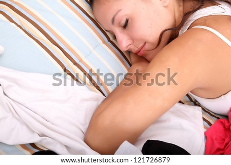 A girl laying in between of a bunch of clothes. - stock photo