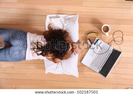 A girl laying on the Floor while surfing on the Internet with a Laptop. - stock photo