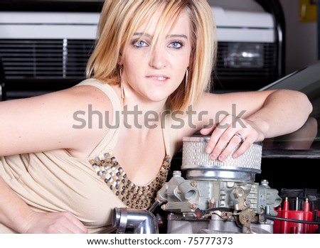 A girl leans on the motor of a vehicle and looks through the viewer.