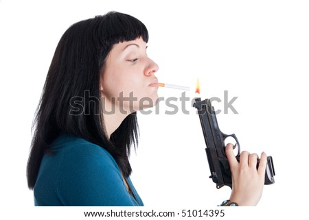 A girl lighting a cigarette with a gun-shaped lighter. - stock photo