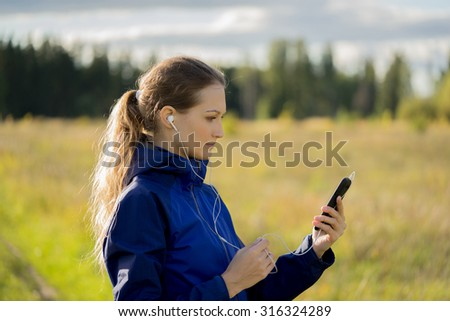 A girl looking at smart phone and listening music outside
