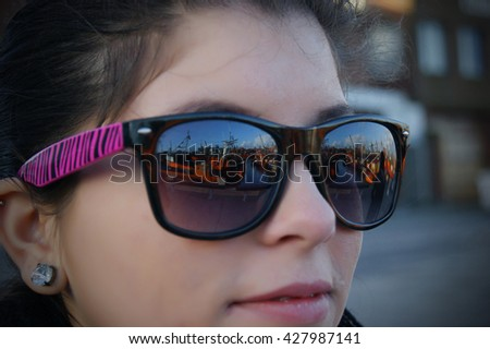 A girl looking at the typical orange fishing boats on the port of the coastal city of  Mar del Plata, Argentina with a reflection in her glasses - stock photo