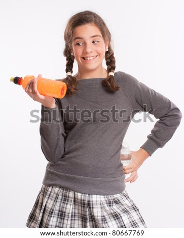 A girl looking longingly at a soda bottle she is holding in her hand - stock photo