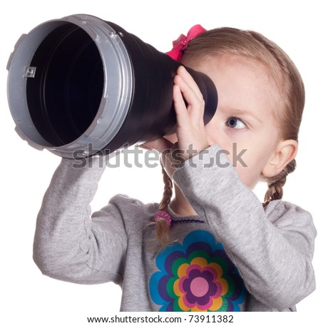 A girl looking through a metal cone.  She is make believing that it is a telescope. - stock photo