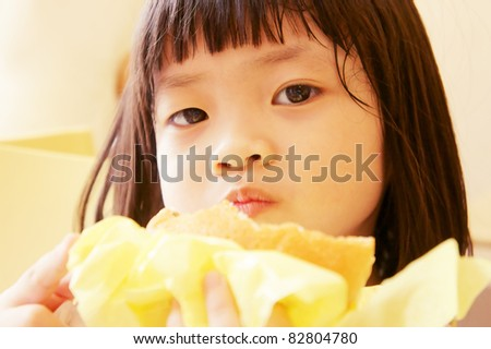 A girl mouthful of burger - stock photo