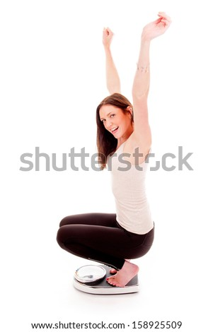 a girl on a weighing scale, celebrating her success of loosing weight