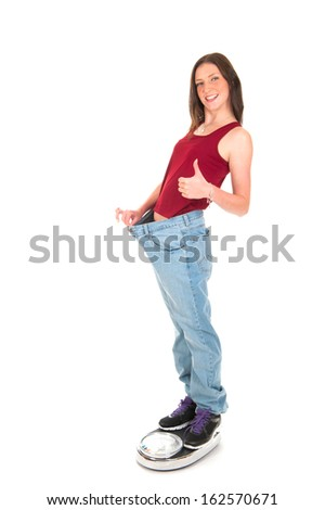 a girl on a weighing scale, celebrating her success of loosing weight - stock photo