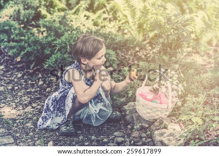 A girl on an Easter egg hunt looks at an egg from her basket outdoors in a garden during the spring season.  Part of a series.  Filtered for a retro, vintage look. - stock photo