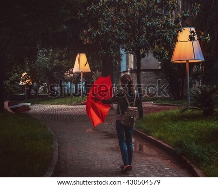 A girl opening a red umbrella during a rainy evening in Tirana The city is decorated with large street lamps.