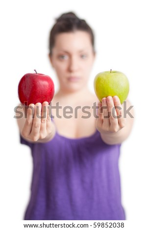 A girl (out of focus) is offering two apples (in focus). One is red, the other one is green - which one will you choose? - stock photo