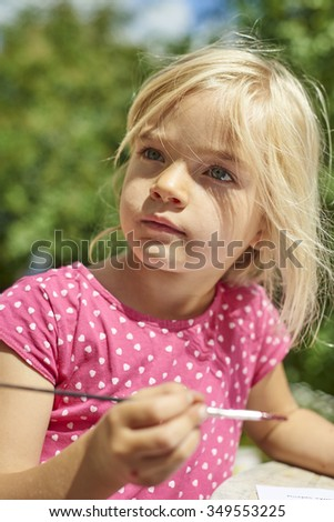 A girl painting with water colors (watercolors), painting a paper plate with watercolour paints outside in garden