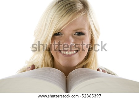 A girl peaking over the pages of a book. - stock photo