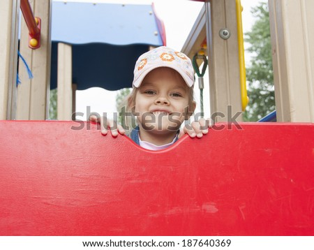 A girl peeks out from the top of the shield, while on the Playground. The girl is wearing a cap.