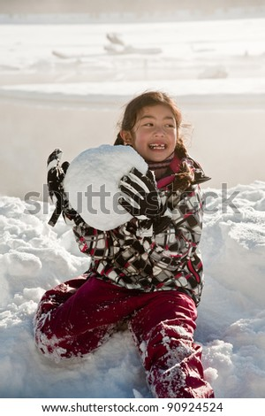 A girl playing with a snowball by a lake