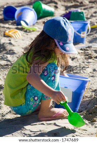 A girl plays in the sand. - stock photo