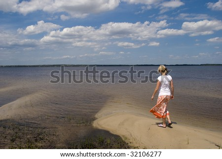 A girl posing with a lake and blue sky in the background. - stock photo