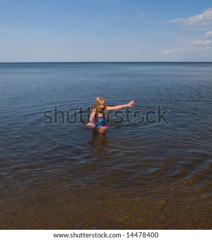A girl racing to get out of the freezing water of Lake Superior