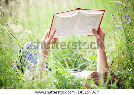 a girl reading a book lying in meadow grass - stock photo