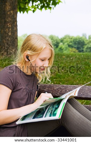 A girl, reading a newspaper while listening Musik - stock photo