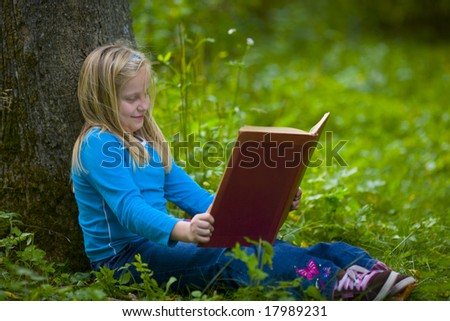 A girl reading under a tree in a green outdoor scene - stock photo