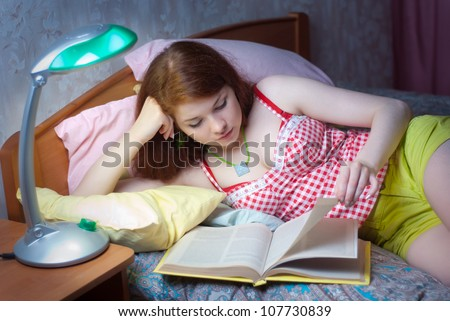 A girl reads a book in bed at night - stock photo