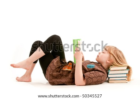 A girl reads a book resting head om pile of books - stock photo